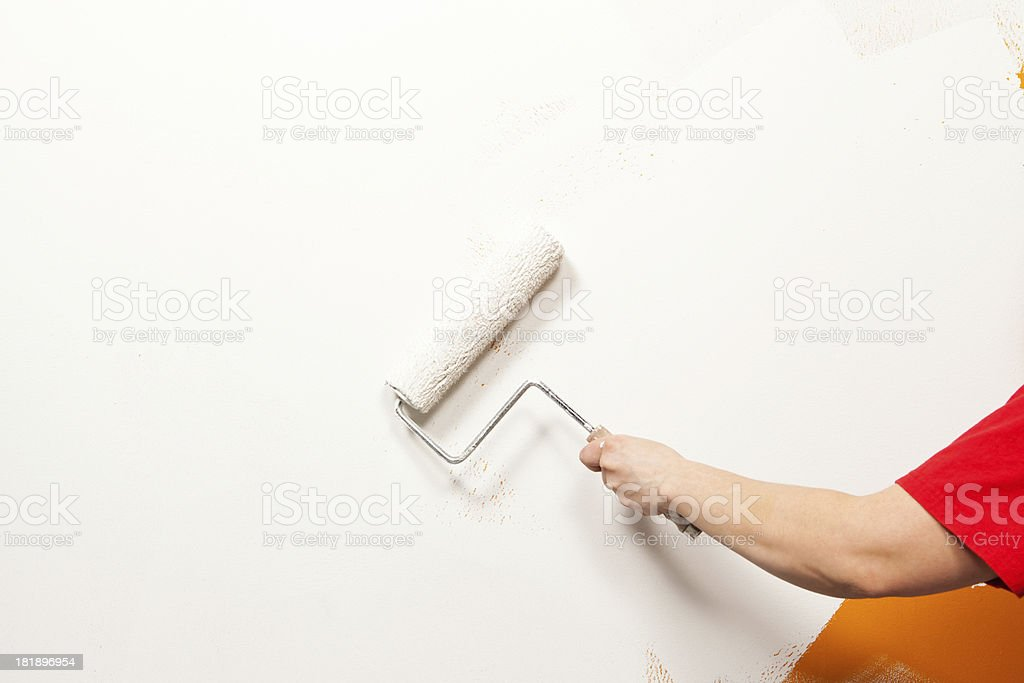Painter Rolling White Paint over Old Orange Wall royalty-free stock photo