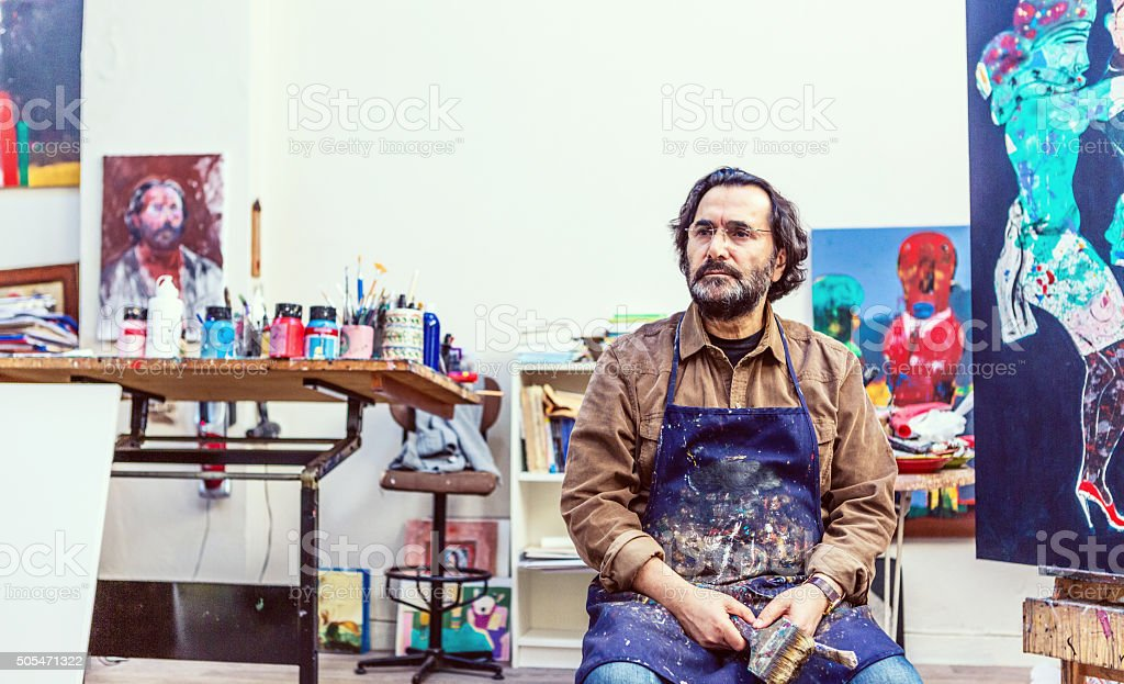 Painter Sitting Front of Easel in Art Sudio stock photo