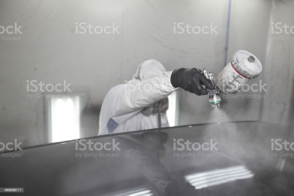 Painter spray-painting the roof of a car stock photo