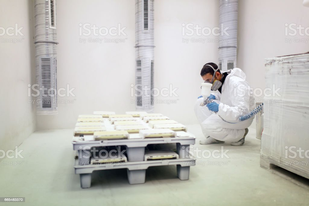 Painter using airbrush to paint wearing protective clothing stock photo