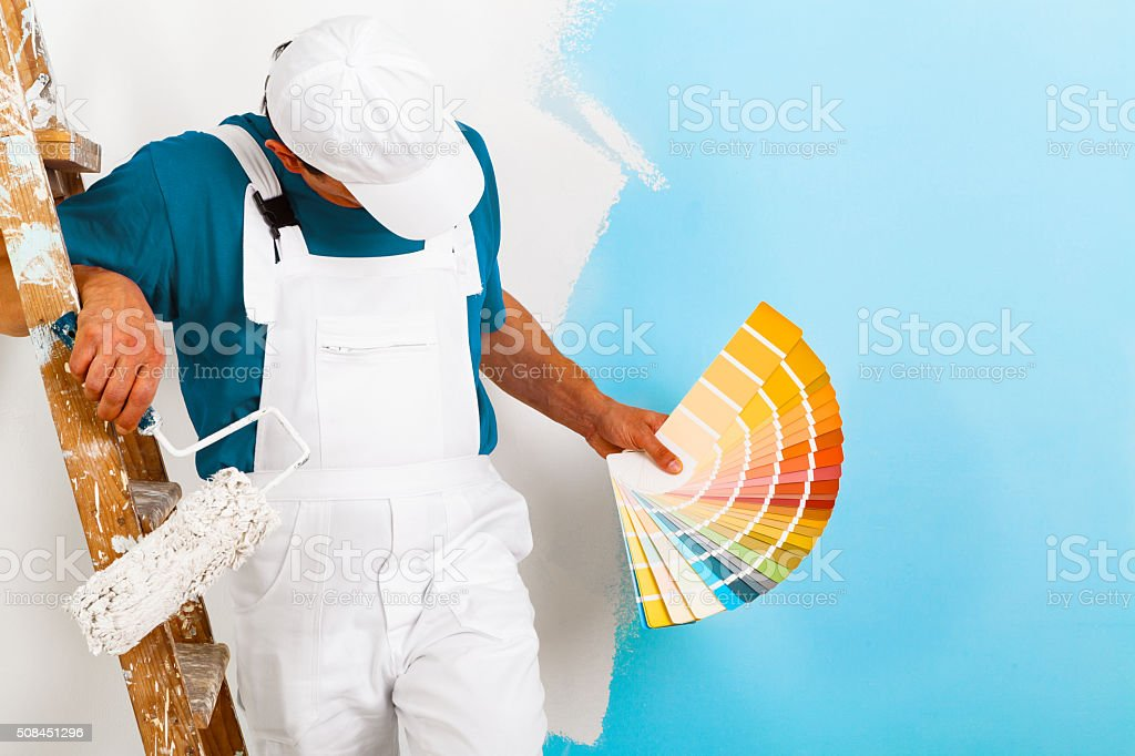 painter  with paintroller showing a color palette stock photo