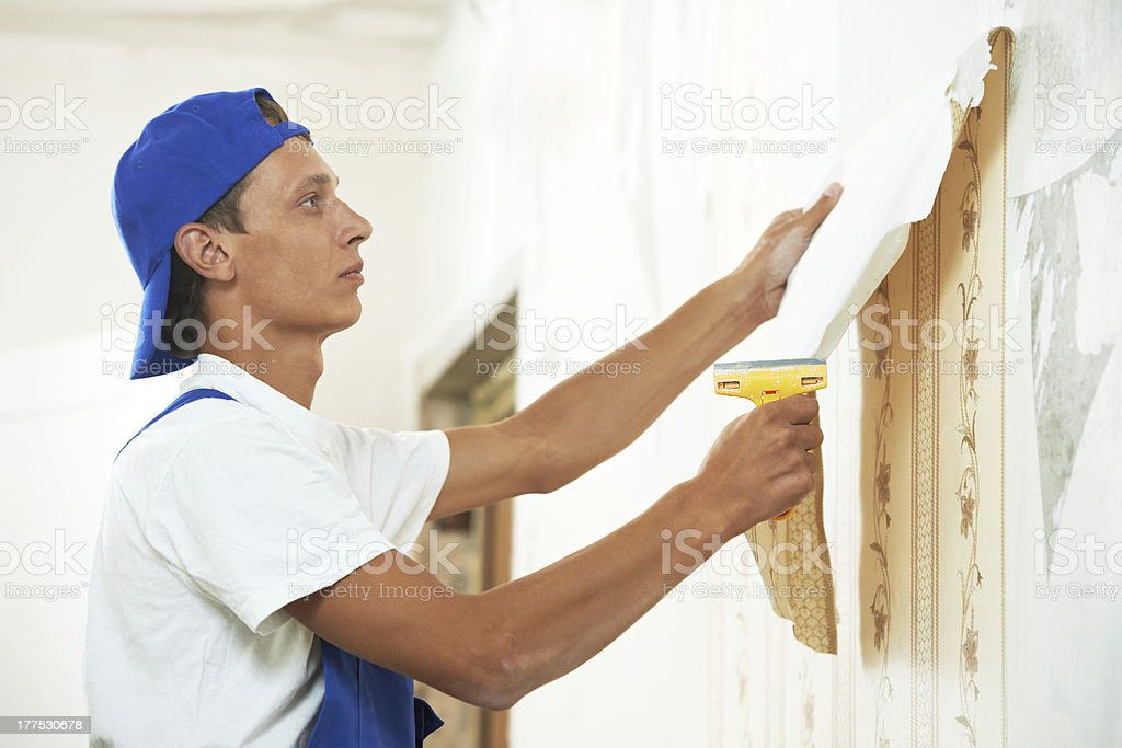 painter worker peeling off wallpaper stock photo