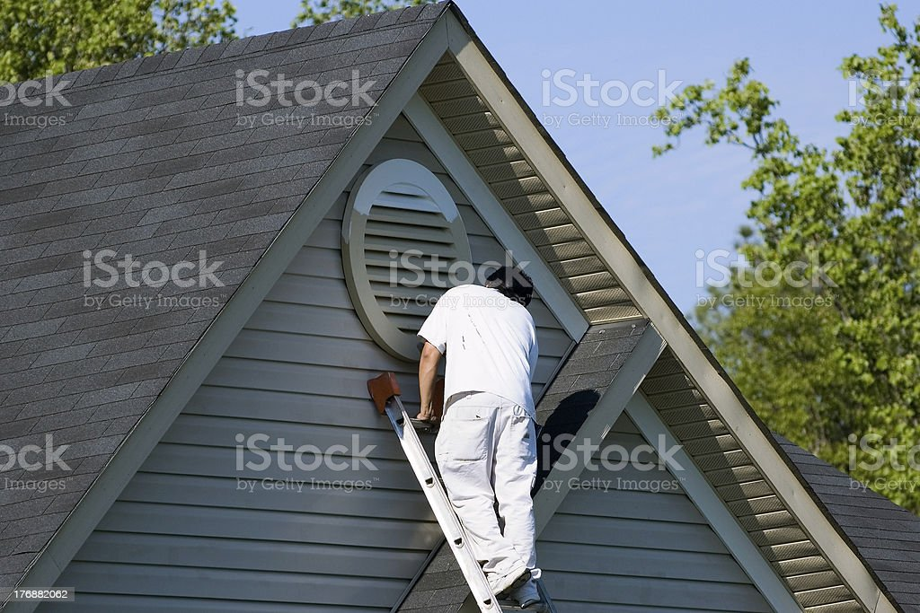 Painter working at roofline stock photo