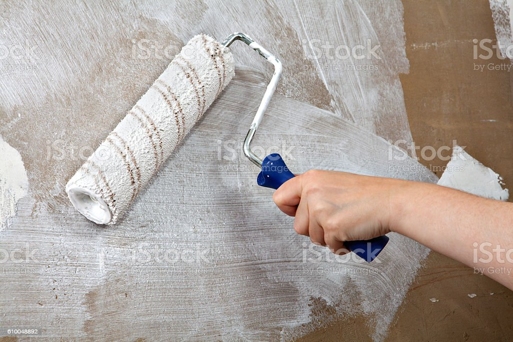 Painters hand holds paint roller, painting wall with white color stock photo