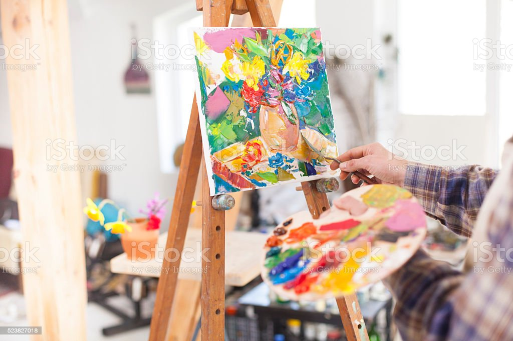 Painter's palette and new artwork on easel stock photo