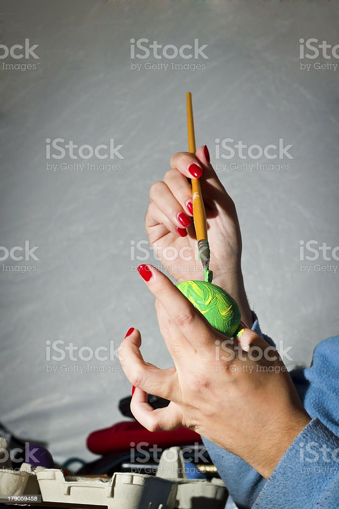 Painting a green easter egg royalty-free stock photo