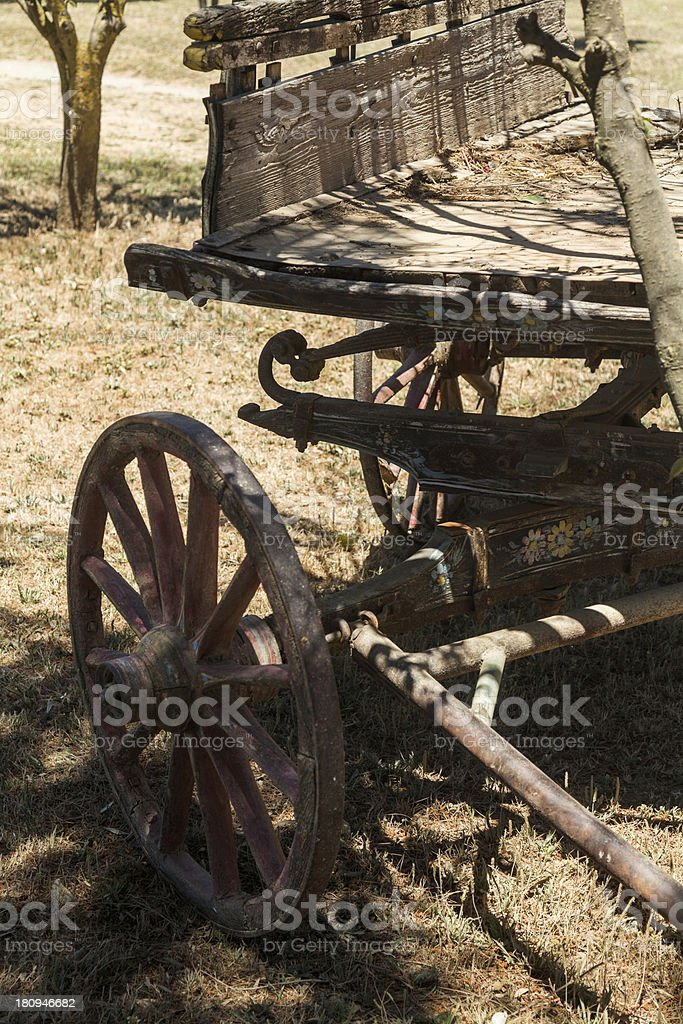 Painting antique wooden cart with big wheels on harvest. royalty-free stock photo