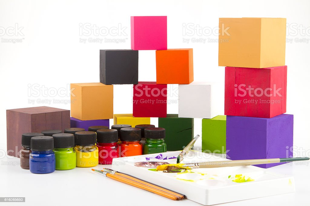 Painting brushes, wooden blocks and paint bottles isolated stock photo