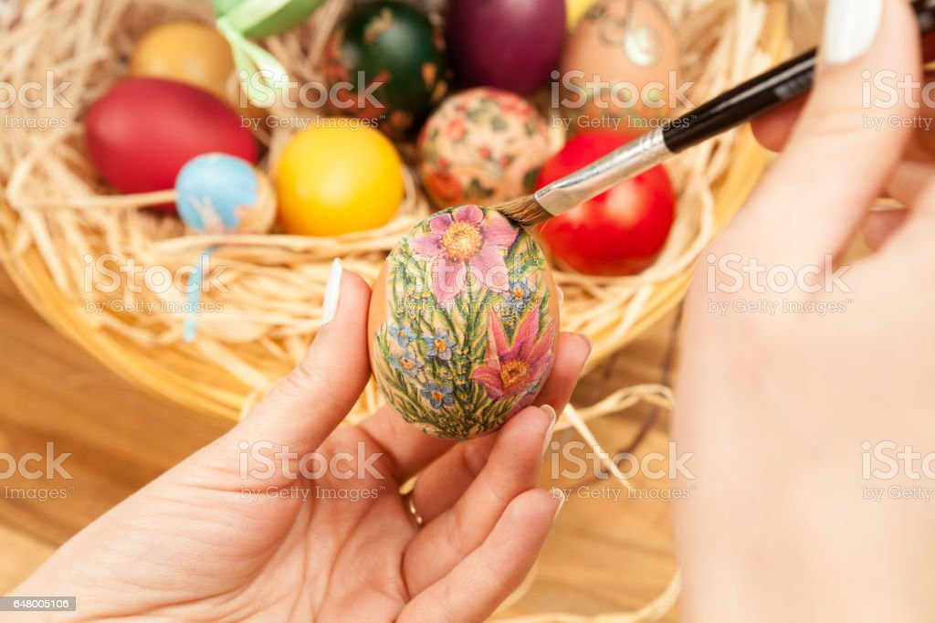 Painting Easter egg with brush. stock photo