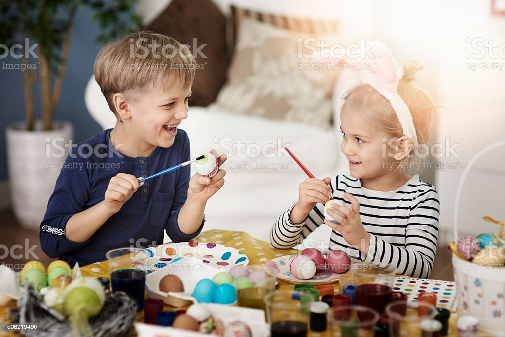 Painting Easter eggs with sister stock photo