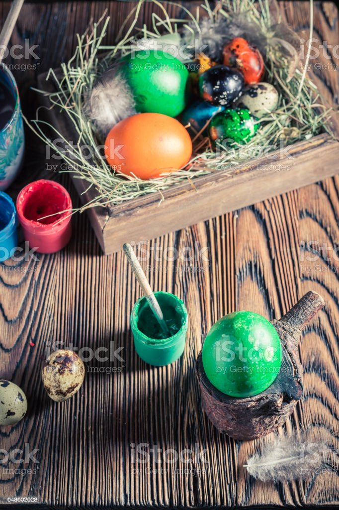 Painting eggs for Easter with hay and feathers stock photo