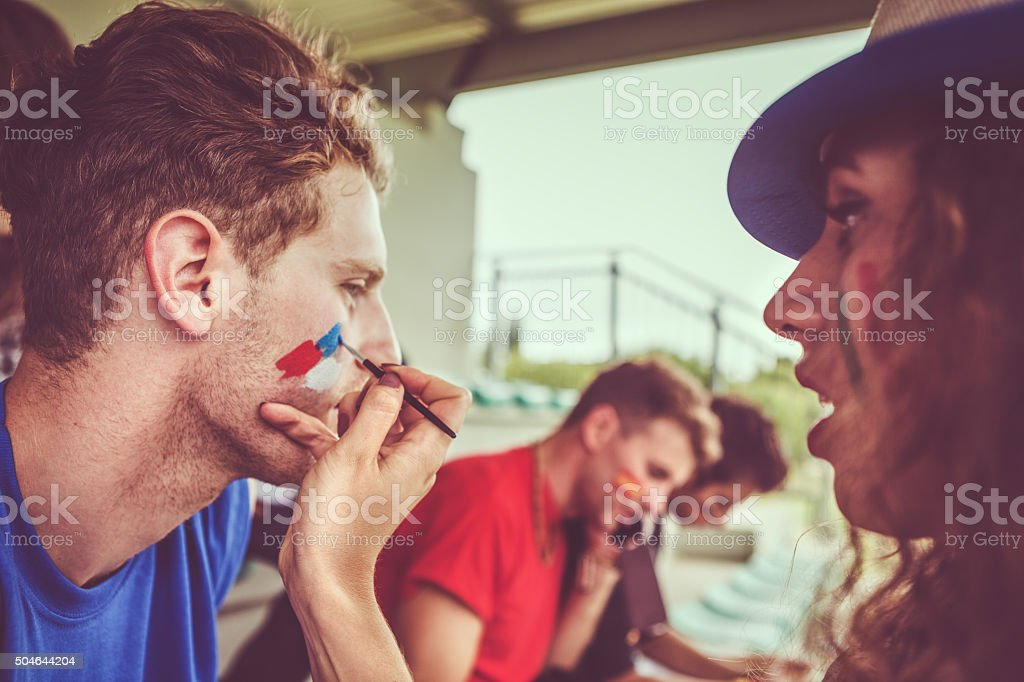 Painting face to sport supporter stock photo