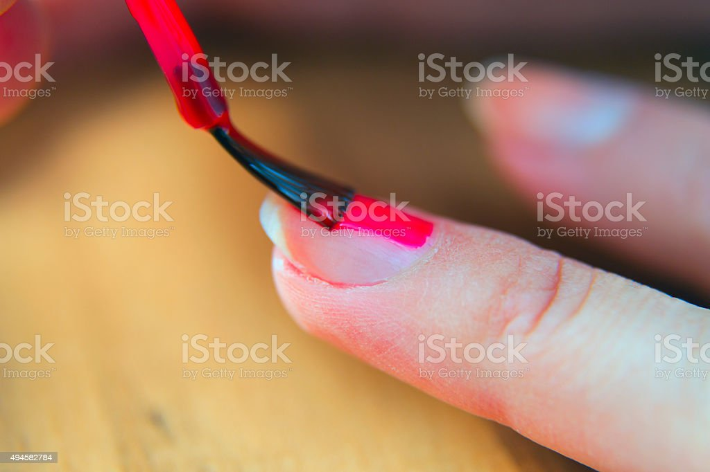 Painting fingernails with red nail polish. stock photo
