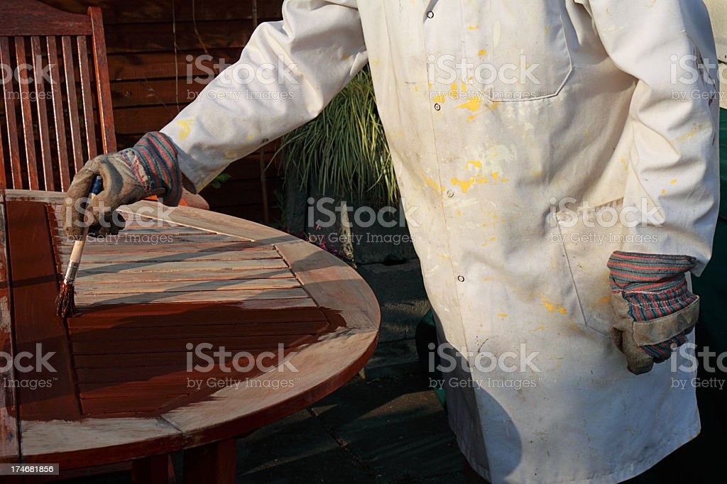 painting garden furniture with wood preservative stock photo