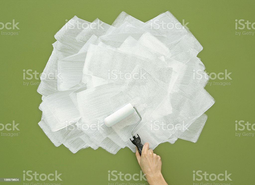 Painting green wall in white color with paint roller royalty-free stock photo
