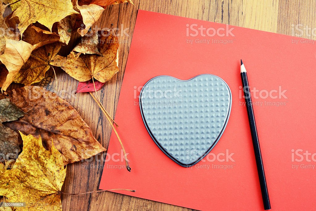 painting heart shape on red paper stock photo