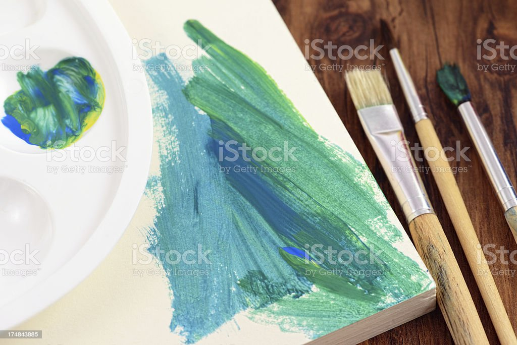 painting of watercolors on a paper pad with paintbrushes stock photo
