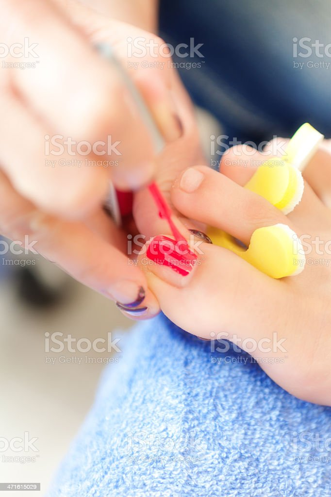 Painting Red Nail Polish on Toes in Spa Vertical royalty-free stock photo