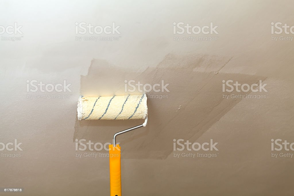 Painting the ceiling a roller with white paint. stock photo