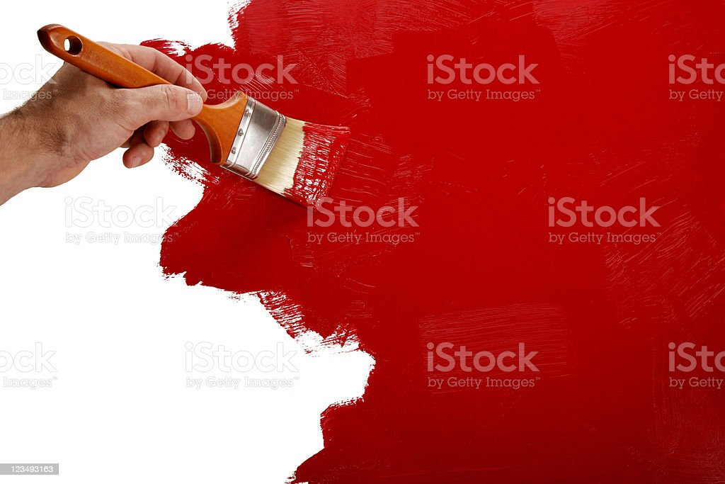 Painting the wall red with a paint brush stock photo