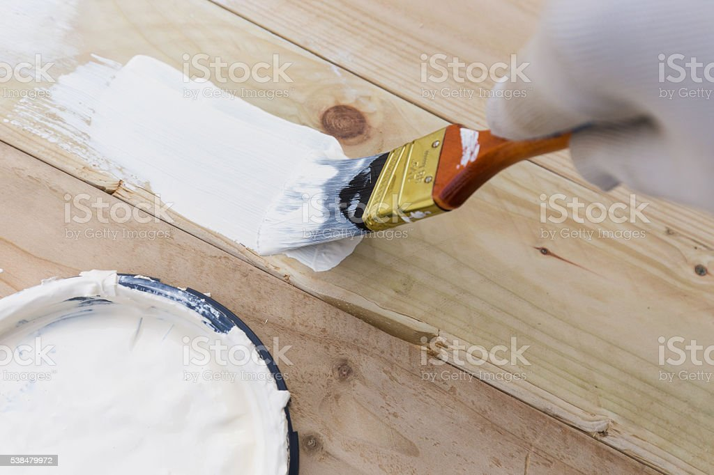 Painting timber boards with the white paint stock photo
