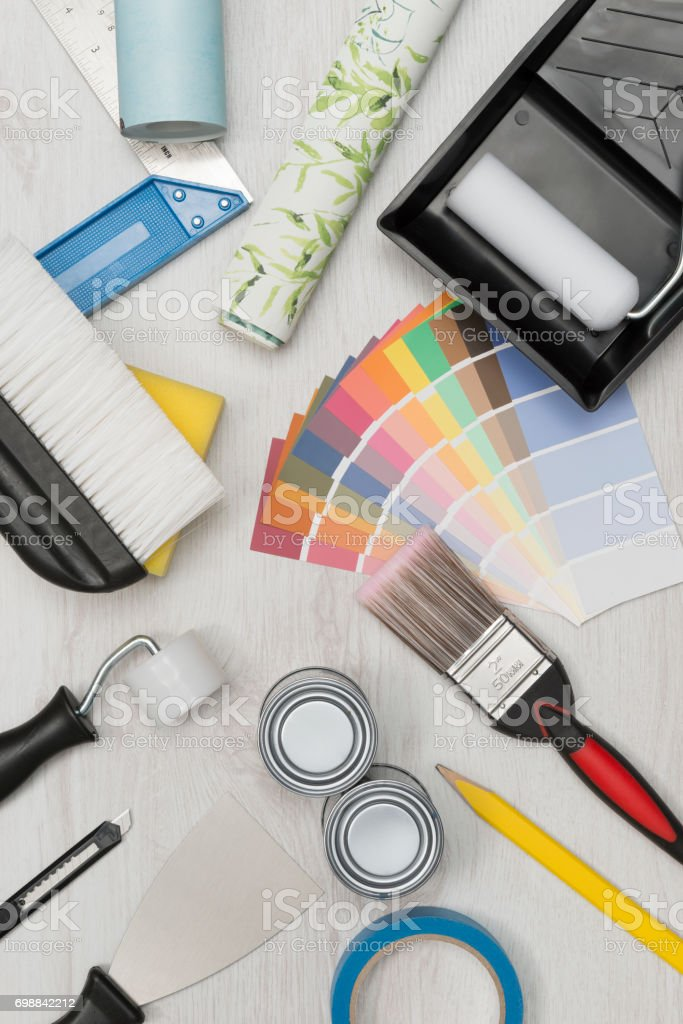 Overhead shot of painting tools including paintbrush, roller, paint...