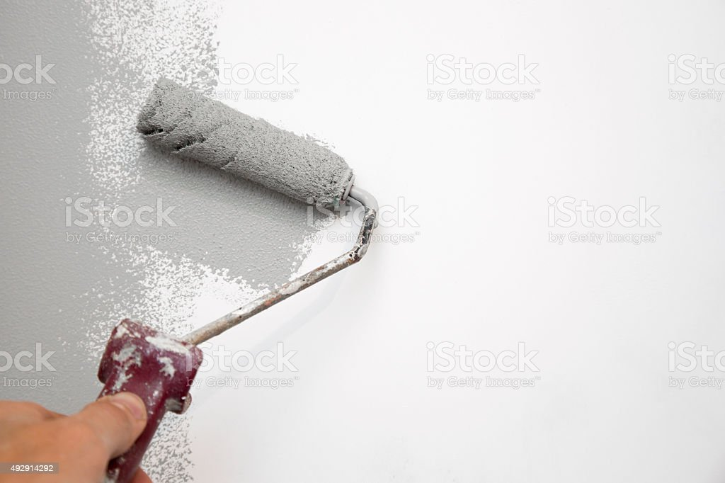 painting wall with roller in hand stock photo