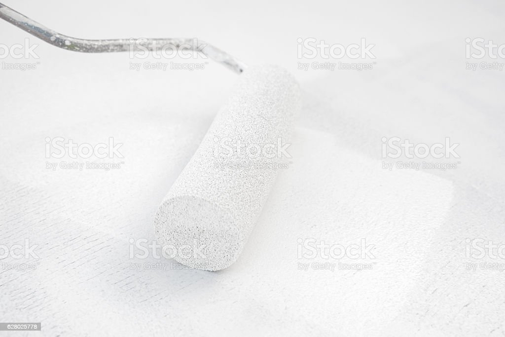 painting white paint with paint roller stock photo