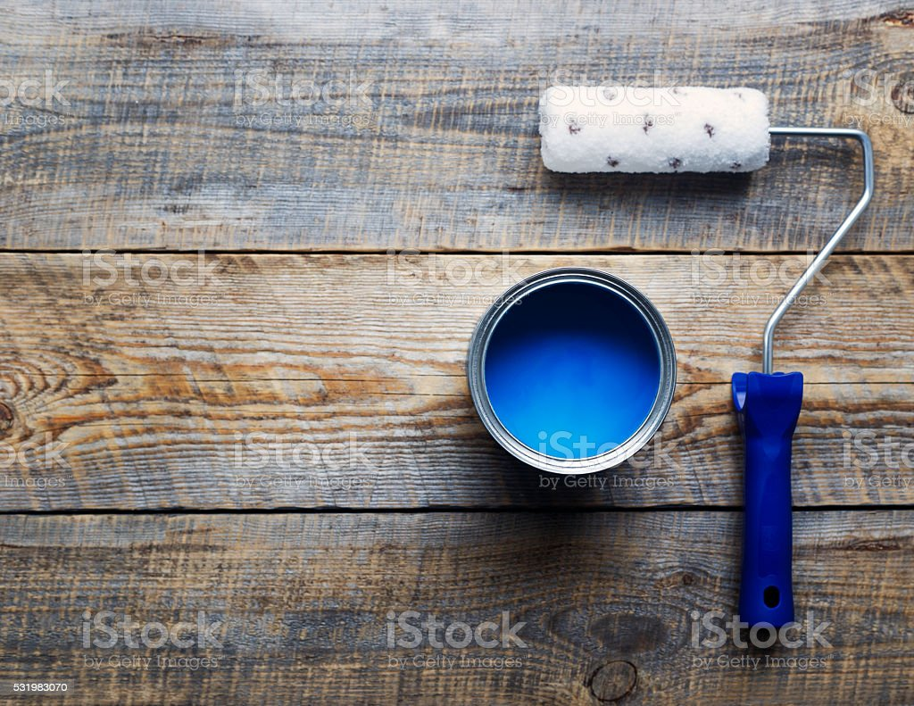 painting with  can of blue paint and roller top view stock photo
