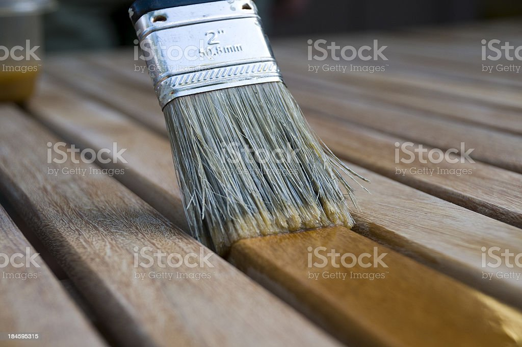 Painting Wood Stain on Patio Set royalty-free stock photo