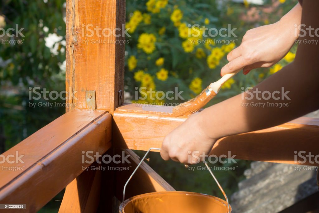Painting wooden fence with brush and paint stock photo