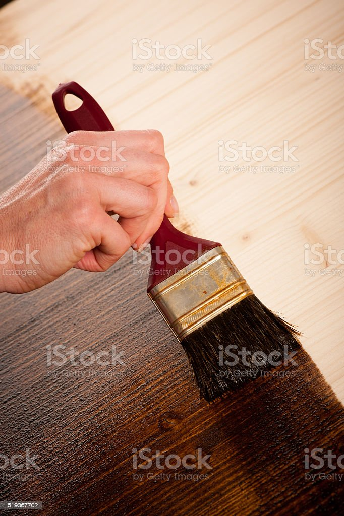Painting wooden table for protection and wood maintenance oil-wax stock photo