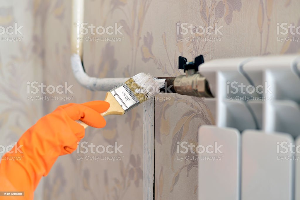 paints a heating radiator in  apartment stock photo