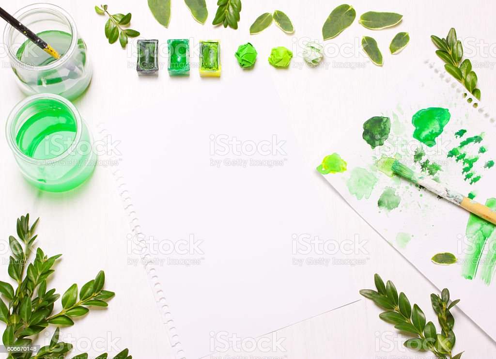 Paints, brushes and green leaves stock photo