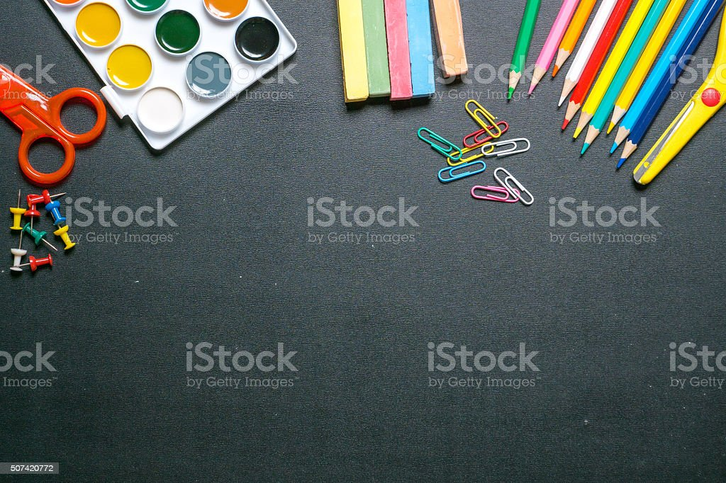 paints, scissors, pencils and chulks on black chalkboard 2 stock photo