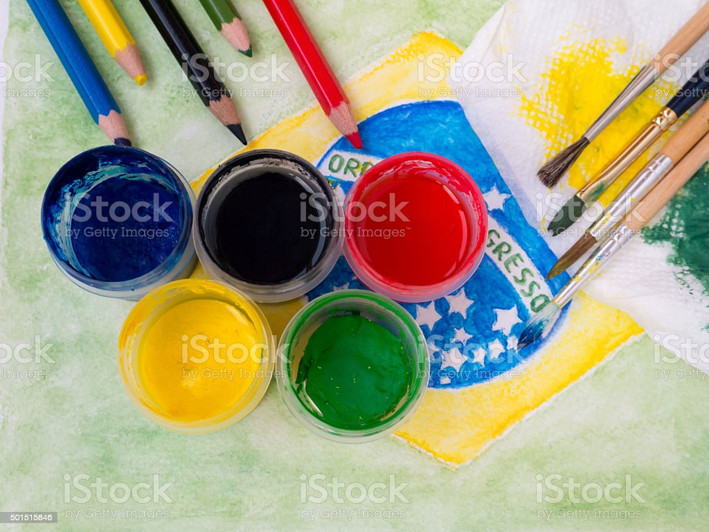 Paints,brushes, pencils  on the brazil flag painting stock photo