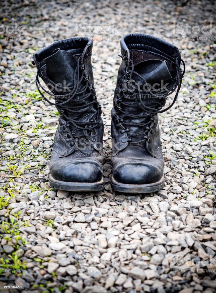 Pair of an old army boots on stones surface, shallow depth of field stock photo