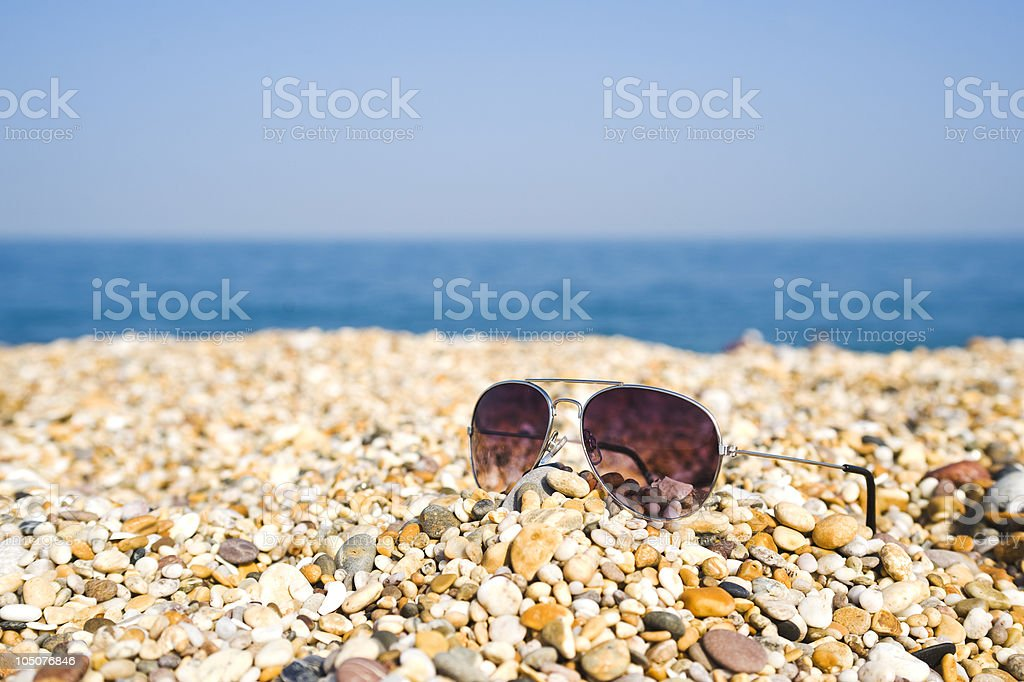 Pair Of Aviator Sunglasses Lying On The Beach royalty-free stock photo