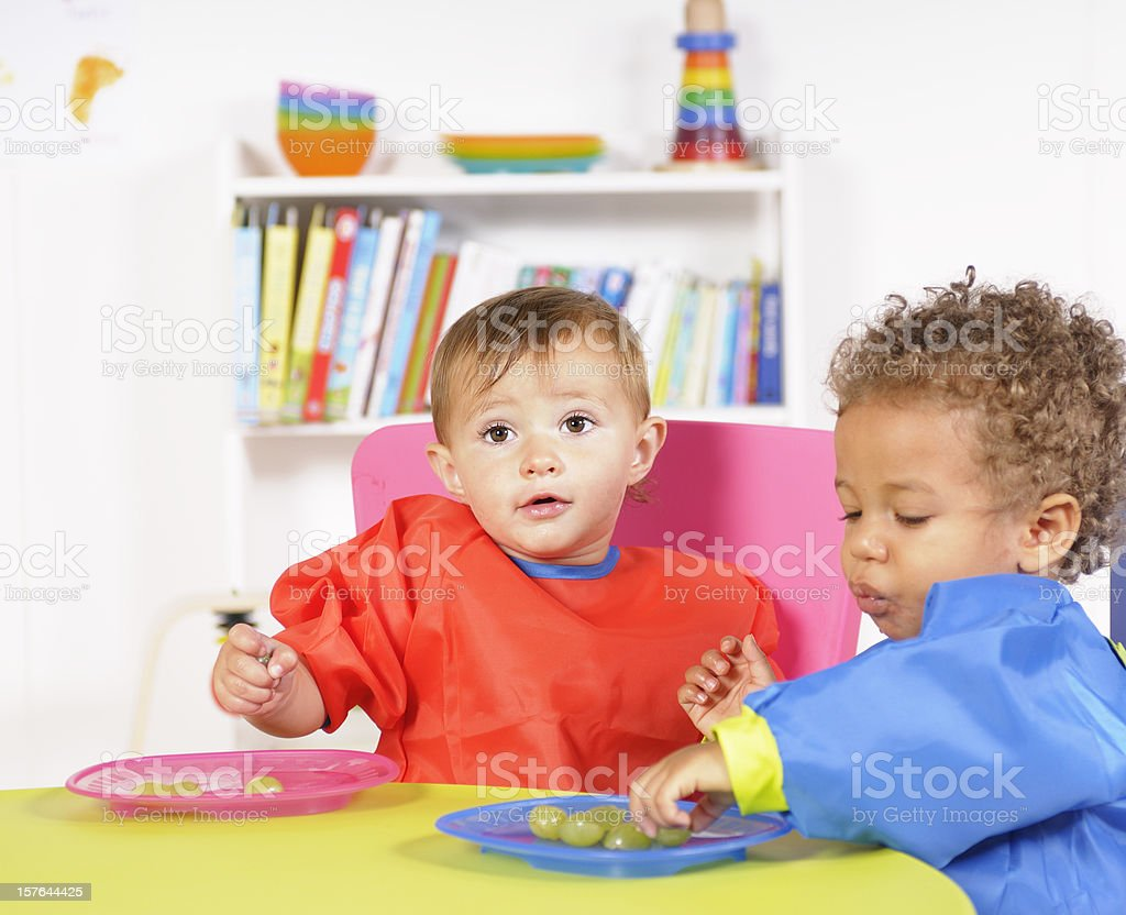 Pair Of Babies Eating Grapes In A Nursery Setting royalty-free stock photo