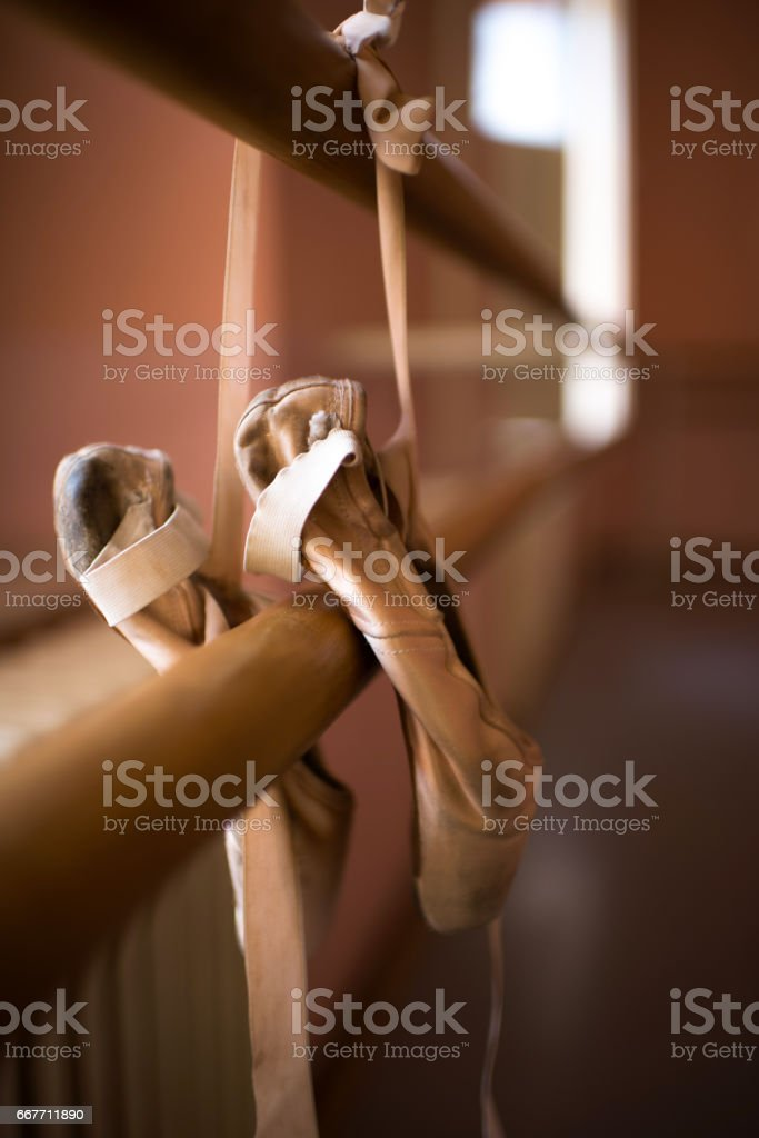 Pair of ballet pumps hanging on barre. stock photo