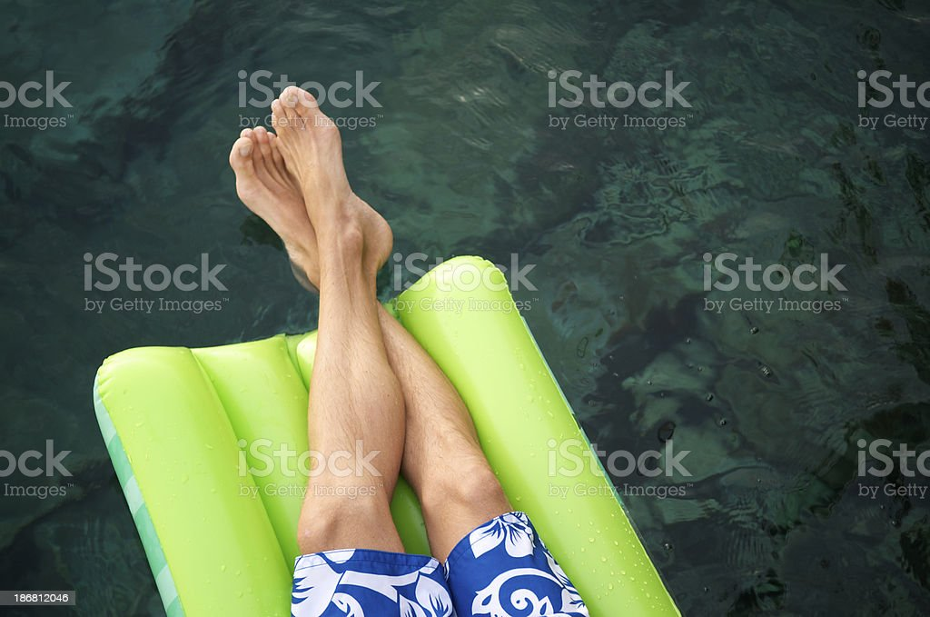 Pair of Bare Feet Float on Pool Raft royalty-free stock photo
