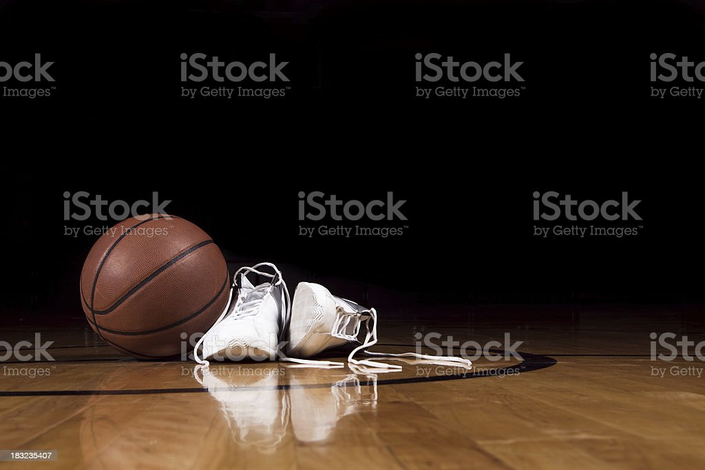 A pair of basketball shoes on a court next to a basketball stock photo
