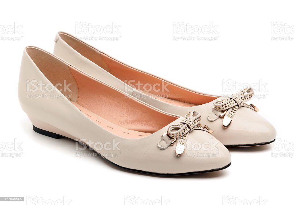 Pair of beige female shoes with bows on over white stock photo