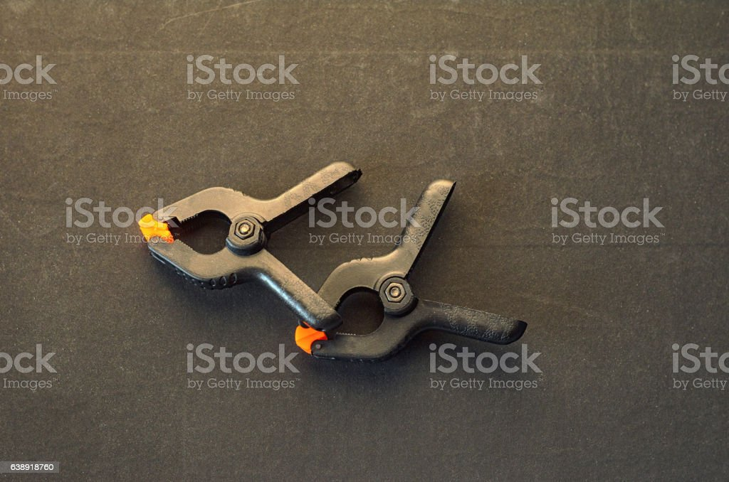 Pair of black clamps  on grey background stock photo