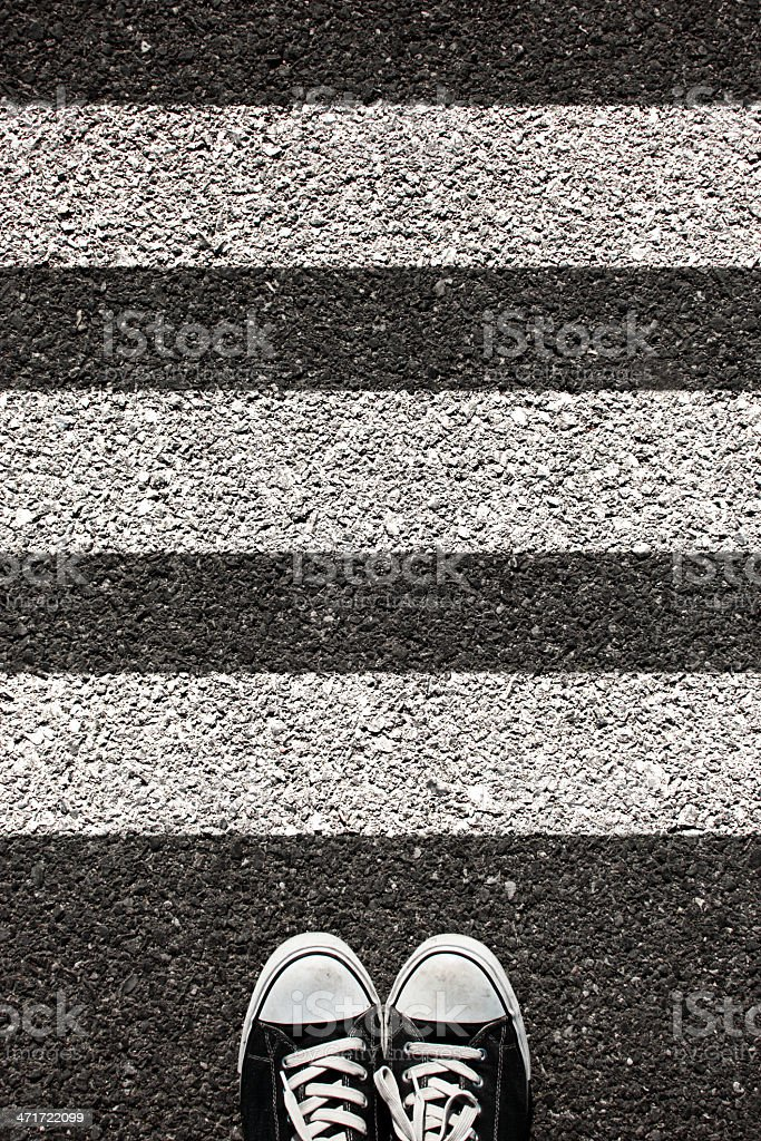 Pair of black sneakers on a paved road with three lines stock photo