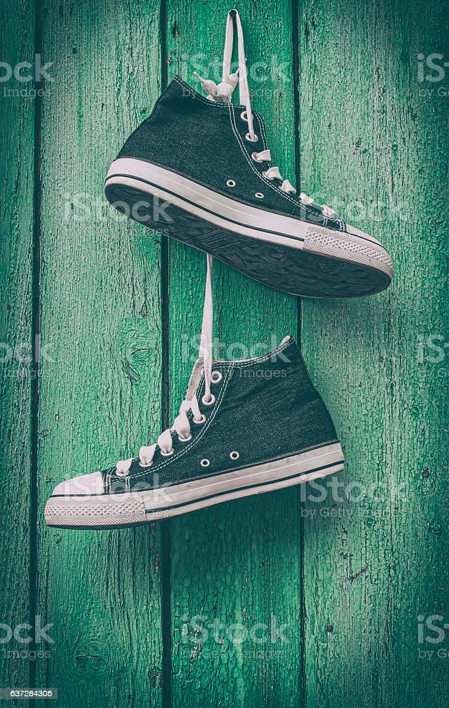 pair of blue men's sneakers hanging laces stock photo