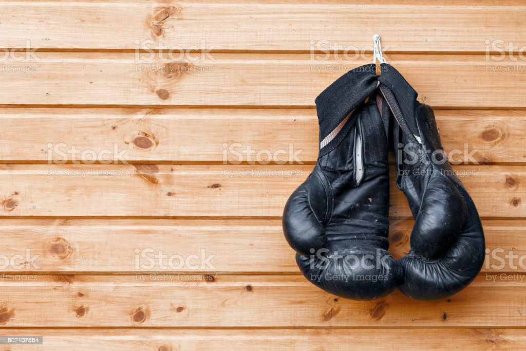 Pair of boxing gloves hanging in a rustic wooden wall. stock photo