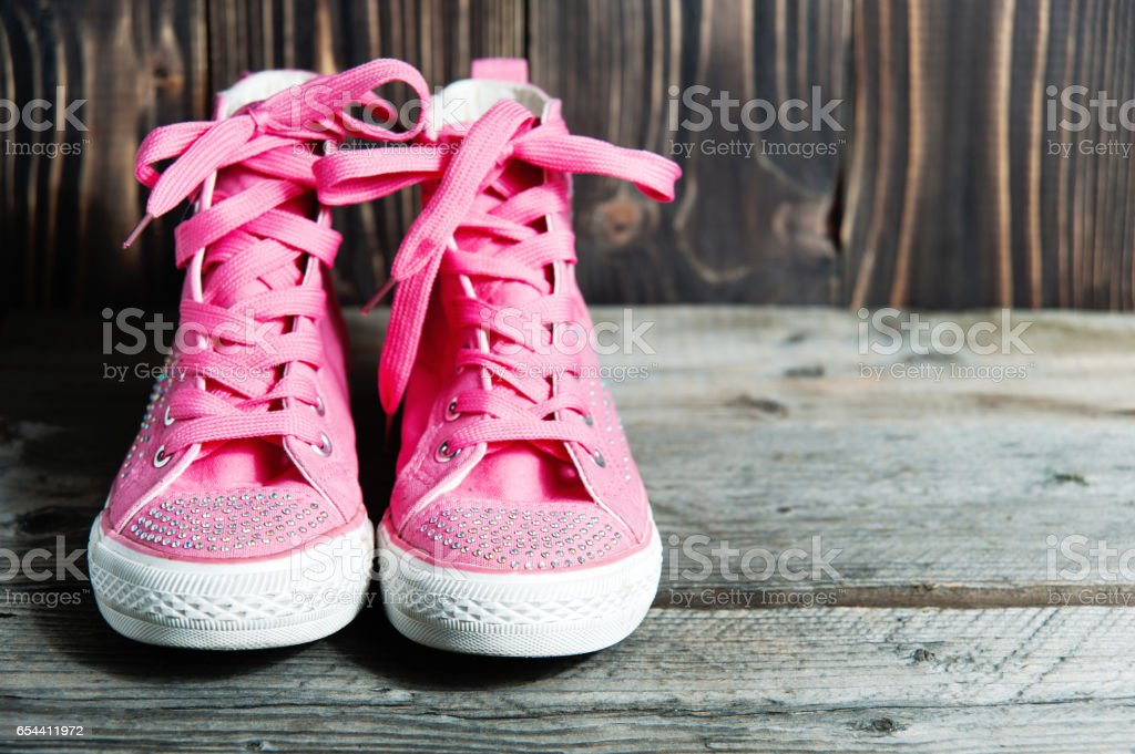 pair of bright pink sports sneakers on a wooden wall cracked stock photo