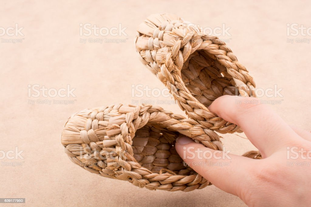 Pair of brown color straw shoes in hand stock photo