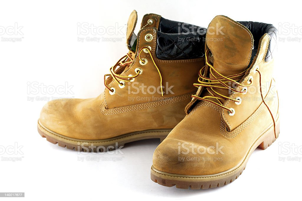 Pair of camel colored work boots on white background stock photo